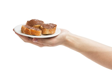 nit: baguette slices spread with nut-choco paste in man hand, isolated on white Stock Photo