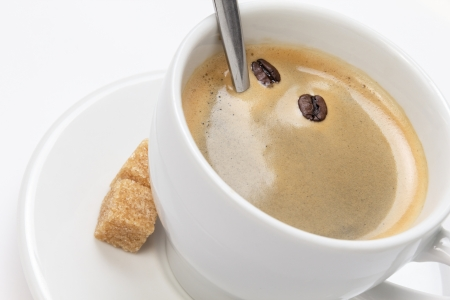 close up of espresso cup with crema, isolated on white background