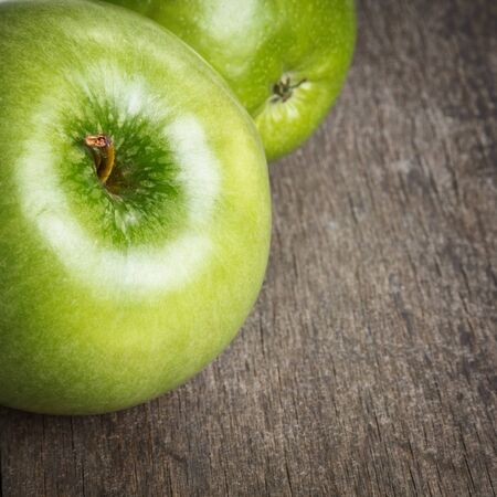 two ripe green apples close up, on old wood table photo