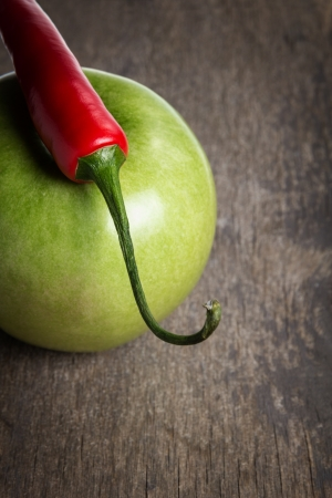 ripe green apple and chili pepper close up, on old wood table photo