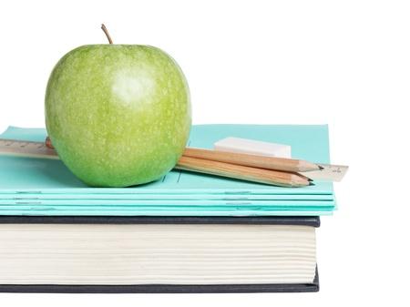 utiles escolares: fuentes de escuela con la manzana en el libro, aislados en blanco
