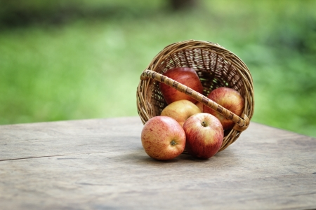 gala apples in a wicker basket, on wooden table Stock Photo - 20356595