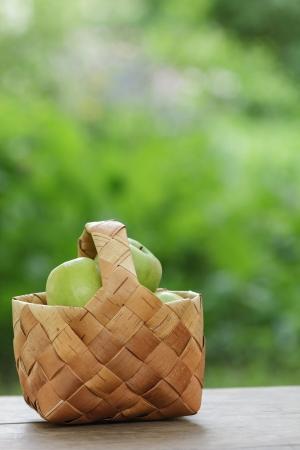 birchbark: green apples in a birchbark basket, on wooden table
