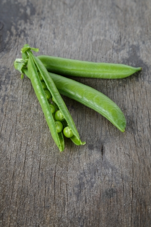 heap of fresh pea pods, on wood table photo