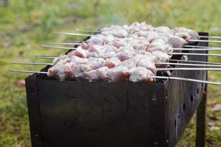 brazier: cooking pork shashlik  on skewer, in brazier outdoors Stock Photo