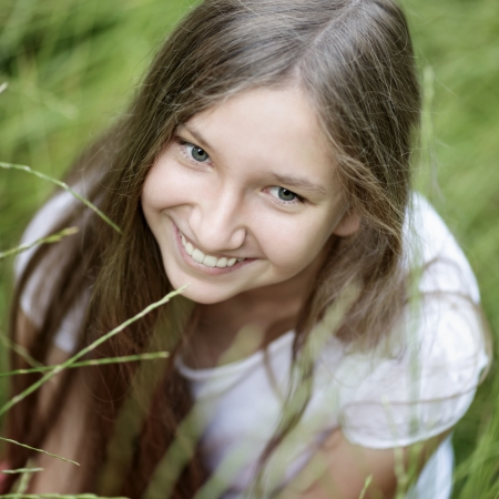 beautiful blonde girl with green eyes: portrait of beautiful teen girl on the grass, upper point