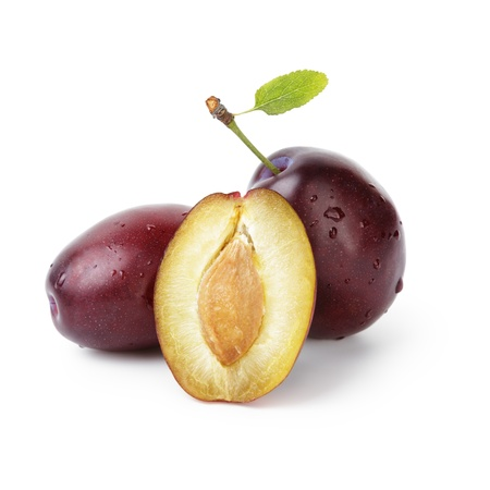 three ripe plums with leaves, isolated on white photo