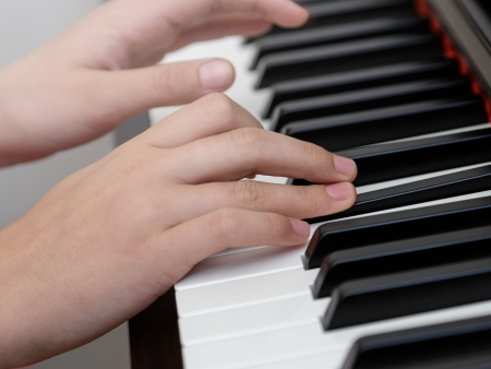 photo of girls hands playing on piano, shallow depth of field photo