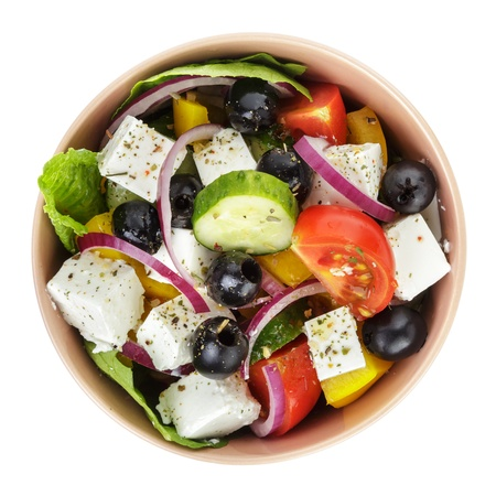 fresh greek salad in clay bowl, isolated on white photo