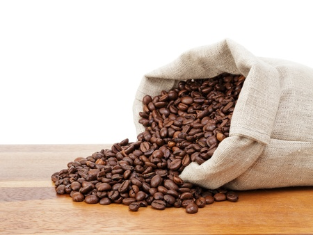 roated coffee beans spill out of the bag, white background photo