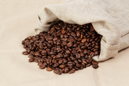 roated coffee beans spill out of the bag, textile photo