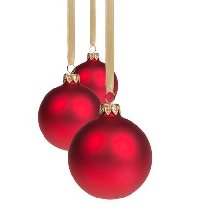 three red christmas balls hanging on ribbon, isolated on white Standard-Bild
