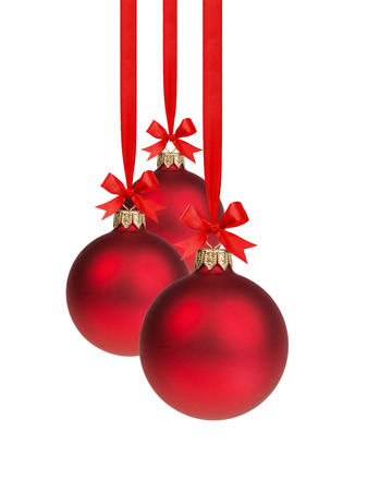 composition from three red christmas balls hanging on ribbon, white background