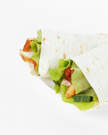 wheat tortilla with chicken and vegetables on plate photo