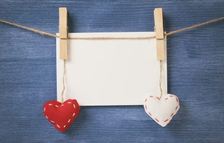 decorative hearts hanging on the rope against blue wood wall, valentine theme photo