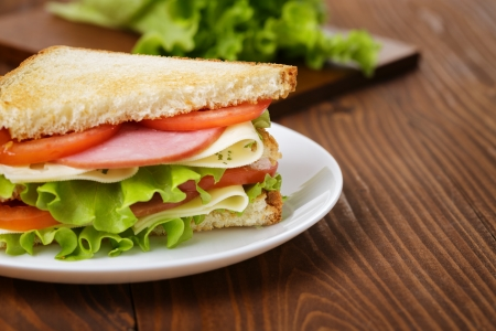 toasted sandwich: toasted sandwich with ham, cheese and vegetables, on wooden table