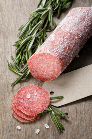 italian salami sausage slices with rosemary and sea salt, wood board photo