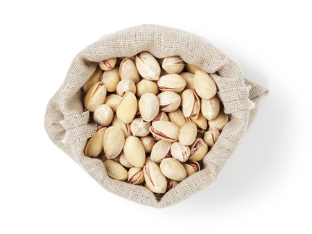 roasted salty pistachios nuts in sack bag from above, isolated on white background photo