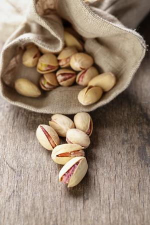 roasted and salted pistachios pour out of the bag, rustic style Stock Photo