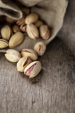 pista: roasted and salted pistachios pour out of the bag, rustic style Stock Photo