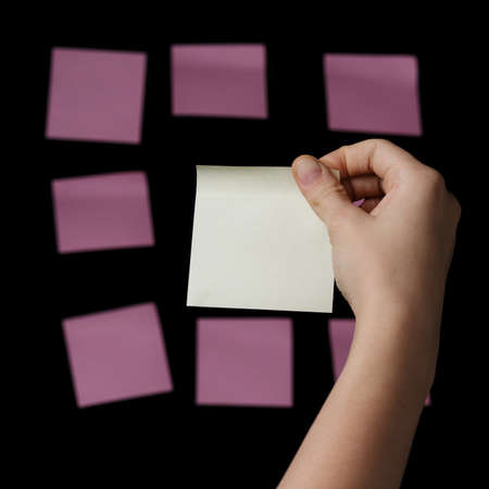 female teen hand holding yellow sticky note agains pinks, isolated on black photo