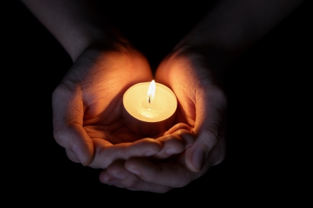 female teen hands holding burning candle in the dark