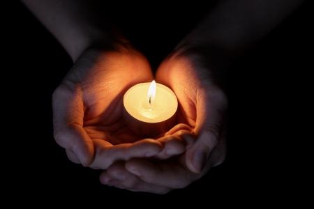 weiblichen Teenager Hände, die brennende Kerze in der Dunkelheit Lizenzfreie Bilder