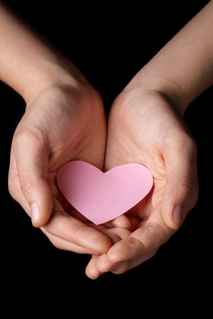 female teen hands holding heart paper, isolated on black photo