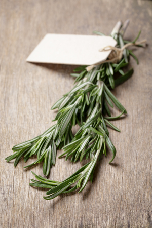 fresh rosemary bunch, on wooden table photo