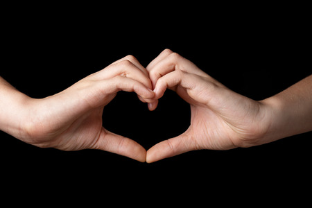 female teen hands showing heart symbol, isolated on black photo