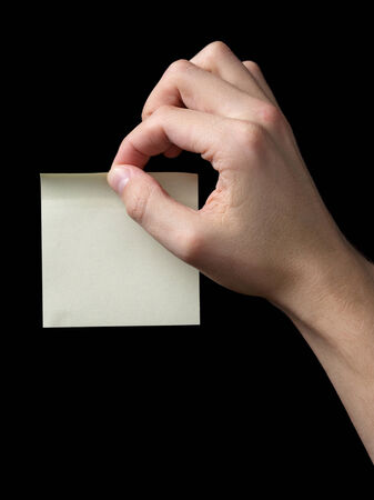 adult man hand holding sticky note, isolated on black photo