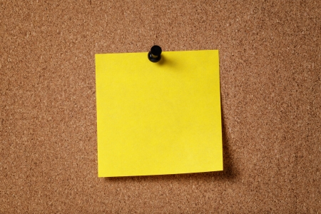 yellow reminder sticky note on cork board, empty space for text photo