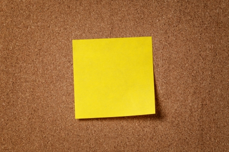 cork board: yellow reminder sticky note on cork board, empty space for text