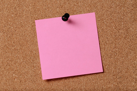 pink reminder sticky note on cork board, empty space for text photo