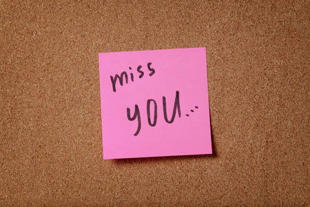 pink reminder sticky note on cork board miss you phrase photo