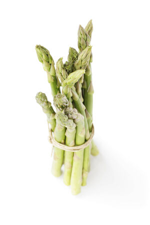 ange: uncooked green asparagus tied with twine, isolated on white