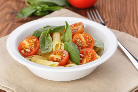 simple italian pasta penne with tomatoes and basil, on table photo