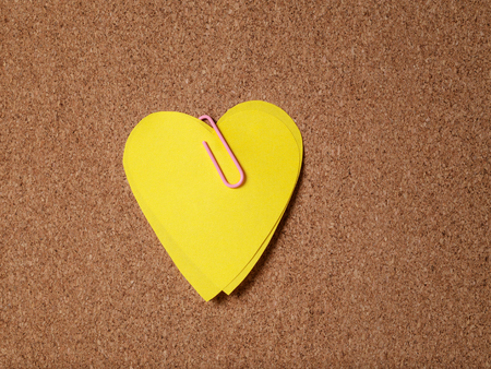 yellow heart shape sticky notes on cork board photo