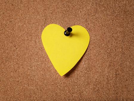 yellow heart shape sticky note on cork board photo