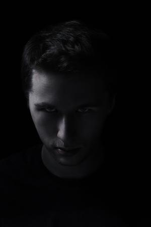 unfreundliche Mann Porträt in der Dunkelheit, leicht getönten