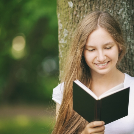 young teenage girl reading book near tree, summertime lifestile photo