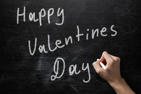 adult male hand write happy valentines day on blackboard photo