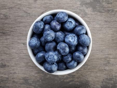 素朴なスタイルの木のテーブル上に白いボールの新鮮なブルーベリー