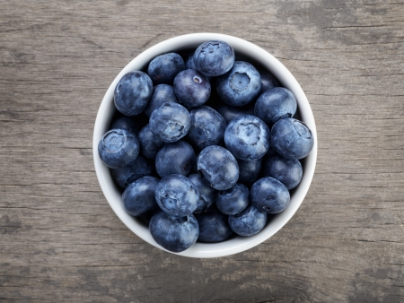 table top view: fresh blueberries in white bowl on wood table, rustic style Stock Photo