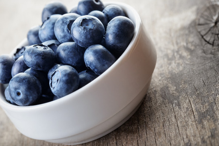 fresh blueberries in white bowl on wood table, rustic style photo