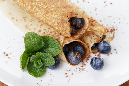 homemade blinis or crepes with blueberries and jam, on wooden table photo