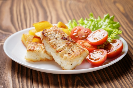 roasted codfish fillet with vegetables, selective focus Stock Photo
