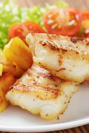 cod fish: roasted codfish fillet with vegetables, selective focus Stock Photo