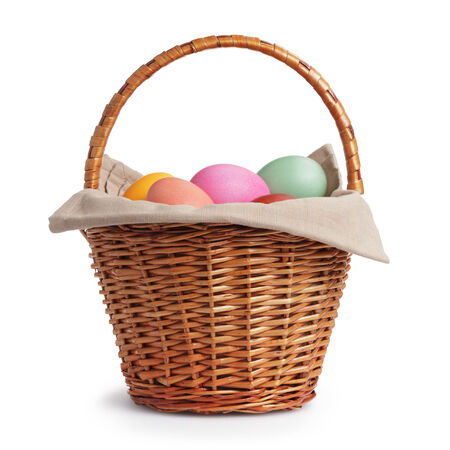 wicker basket full of pastel colors easter eggs, white background photo
