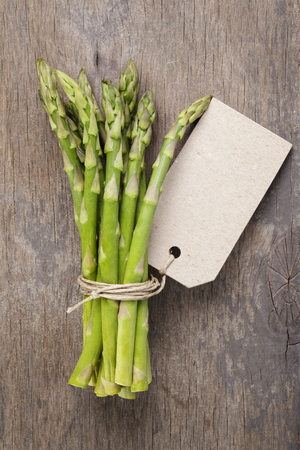 bunch of green asparagus tied with twine and tag, rustic style for market photo